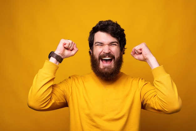 Strong bearded man is making the winner gesture with both hands on yellow background.