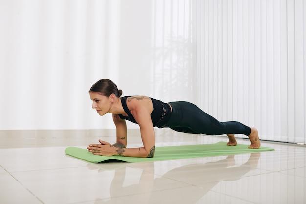 Сильная красивая женщина в спортивной тренировочной одежде делает упражнения на доске на коврике для йоги дома