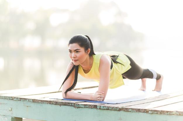 板張りのコア筋肉運動を行う強力な美しいフィットネス屋外、健康的なライフスタイルとダイエットの概念