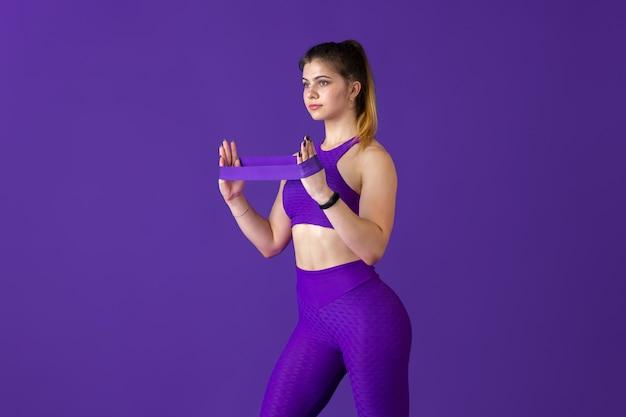 強い。紫のモノクロのポートレートで練習する美しい若い女性アスリート。ゴム入りのスポーティーなコーカサスフィットモデル。ボディビルディング、健康的なライフスタイル、美しさ、アクションのコンセプト。
