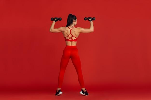 強い。 、モノクロの赤い肖像画で練習している美しい若い女性アスリート。ウェイト付きのスポーティーフィットブルネットモデル。ボディービル、健康的なライフスタイル、美しさとアクションのコンセプト。