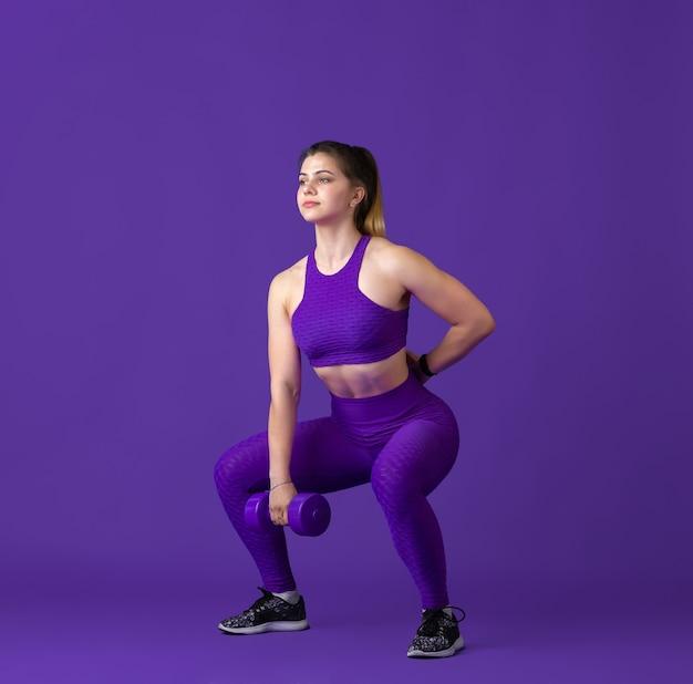 강한. 스튜디오에서 연습하는 아름다운 젊은 여성 운동선수, 단색 보라색 초상화.