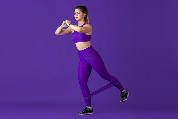 強い。スタジオで練習している美しい若い女性アスリート、モノクロの紫色の肖像画。
