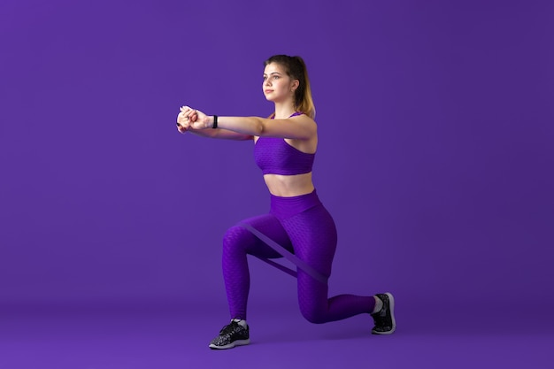 Strong. beautiful young female athlete practicing , monochrome purple portrait. sportive caucasian fit model with elastics. body building, healthy lifestyle, beauty and action concept.