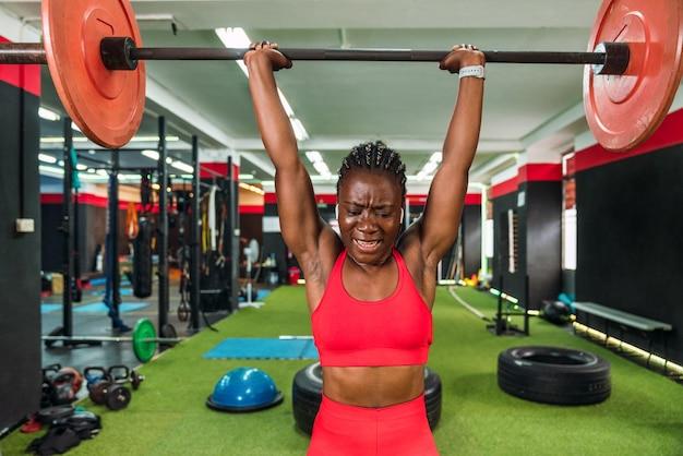 体育館でバーベルやウェイトリフティングのエクササイズをして肩や上腕二頭筋を強化し、多くの努力を示している強い黒人アスリートと赤いスポーツウェア