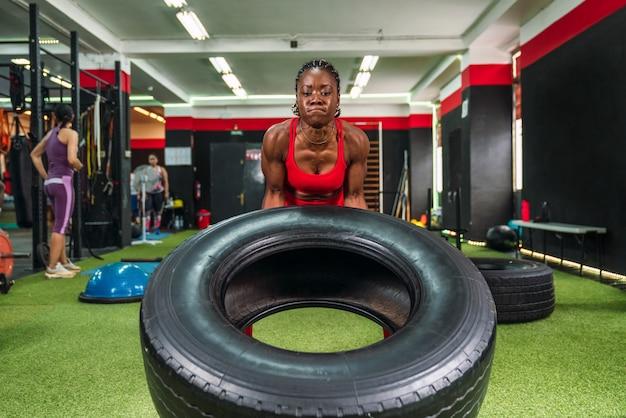 赤いスポーツウェアの大腿四頭筋と上腕二頭筋を強化するためにホイールリフティング運動をしているジムの強い黒人女性アスリート