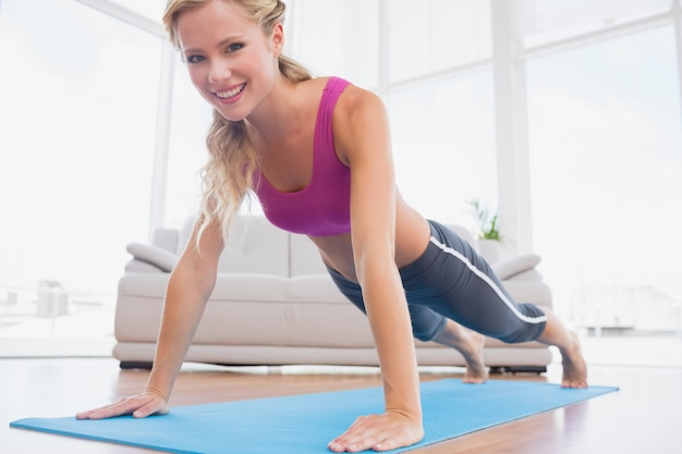 Strong blonde in plank position on exercise mat smiling at camera