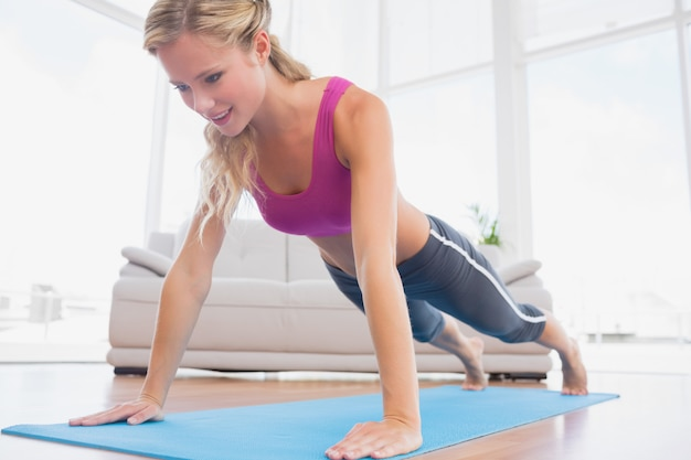 Strong blonde in plank position on exercise mat