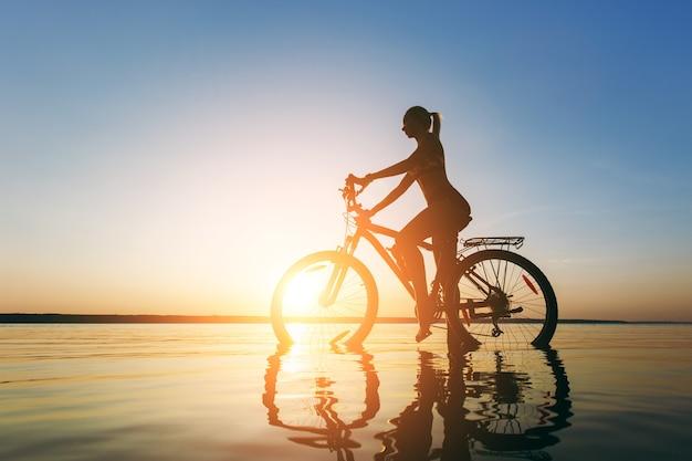 La forte donna bionda in un vestito colorato si siede sulla bicicletta nell'acqua al tramonto in una calda giornata estiva. concetto di forma fisica.