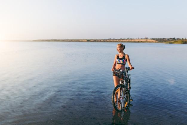 La forte donna bionda in un abito colorato si trova vicino alla bicicletta nell'acqua al tramonto in una calda giornata estiva. concetto di forma fisica.