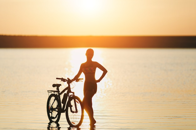 The strong blonde woman in a colorful suit stands near the bicycle in the water at sunset on a warm summer day. fitness concept.