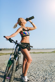 The strong blonde woman in a colorful suit and sunglasses stands near a bicycle, drinks water from a black bottle in a desert area. fitness concept.