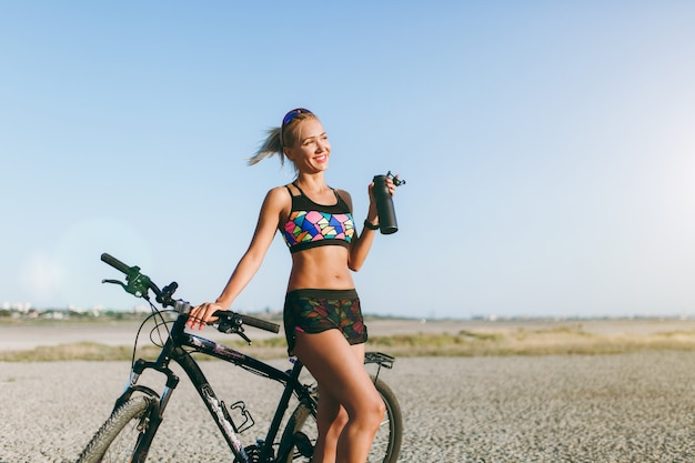 The strong blonde woman in a colorful suit and sunglasses stands near a bicycle with black bottle of water in a desert area. fitness concept.