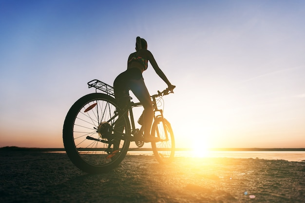 The strong blonde woman in a multicolored suit sits on a bicycle in a desert area near the water and looks at the sun. fitness concept. back view