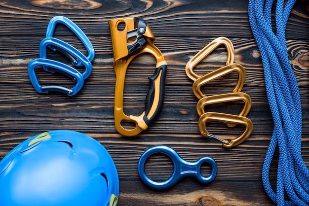 Сильный защитный шлем синего цвета. изолированное альпинистское снаряжение. части карабинов лежат на деревянном столе.