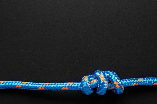 Сильный синий узел веревки на черном фоне пространства копии
