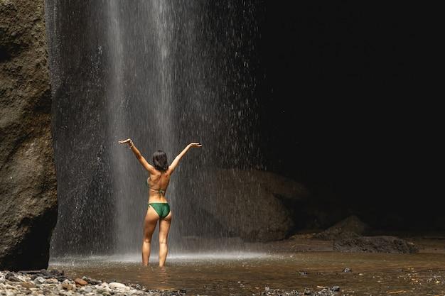 강한 몸. 동굴 근처 찬물에 서서 팔을 들고 있는 친절한 여성