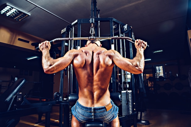 Strong bodybuilder doing exercises at the gym