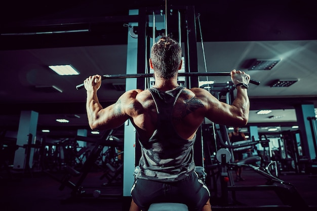 Strong bodybuilder doing heavy weight exercise for back on machine