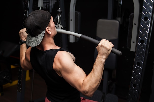 Strong bodybuilder doing heavy weight exercise for back on machine.