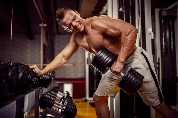 Сильный бодибилдер выполняет упражнения для спины с тяжелым весом с гантелями