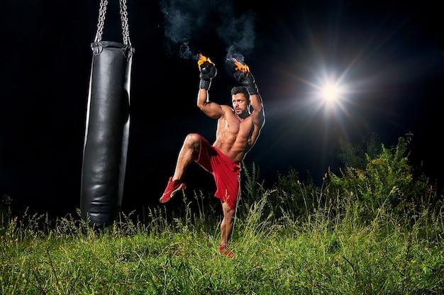 Strong boxer punching sandbag outdoors