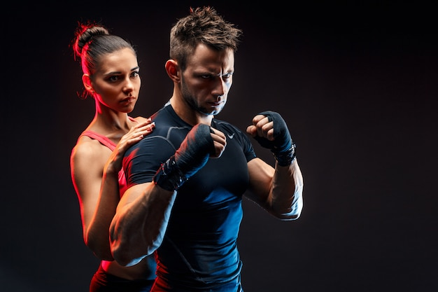 Strong boxer in stance with handwraps on his fists with girlfriend standing behind him.