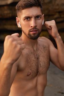 Forte pugile con il corpo nudo, stringe i pugni, esegue esercizi di calcio, allena la boxe all'aperto