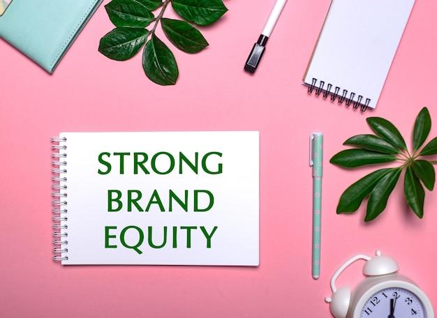 Strong brand equity написано зеленым на белом блокноте на розовом фоне в окружении блокнотов, ручек, белого будильника и зеленых листьев. образовательная концепция