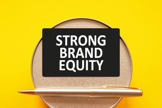 強力なブランドエクイティ-シート紙に白い文字を書く言葉。丸い金属製のスタンドと金属製の筆記ペンが付いた黄色の壁にテキストが書かれた黒いカード。ビジネス、金融、教育の概念 Premium写真