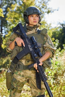 Strong brave female army soldier with rifle machine gun standing in the forest