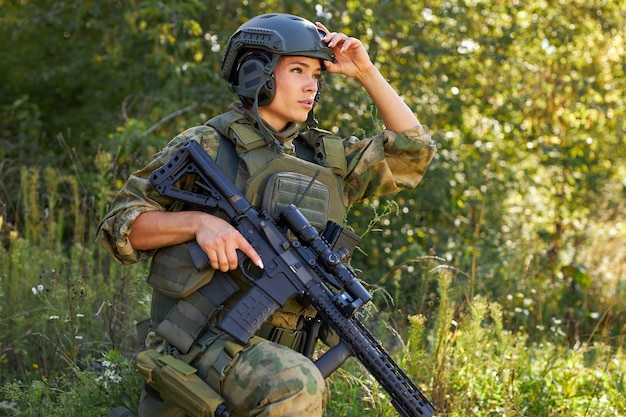 森の中に立っているライフル機関銃を持つ強力な勇敢な女性の軍隊の兵士