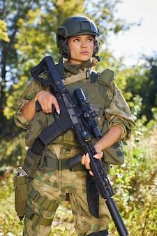 숲에 서있는 소총 기관총을 가진 강한 용감한 여성 육군 군인