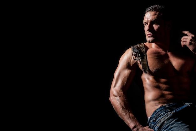 Сильный брутальный парень. сексуальный торс. кожаный ремень, джинсы. красивый большой человек мышц позирует в студии. модель демонстрирует торс с шестью кубиками пресса. изолированные на черном фоне. показаны мускулистый торс.