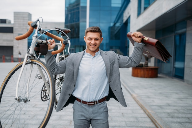 Strong businessman holds bicycle and briefcase at the glass office building in downtown. business person riding on eco transport on city street, urban style