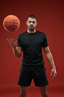 Сильный кавказский баскетболист позирует перед фотоаппаратом
