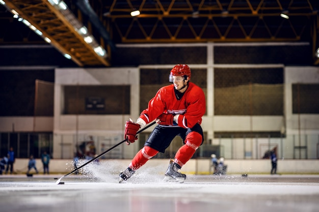 Strong caucasian hockey player in red uniform with helmet skating to goal with stick and puck.