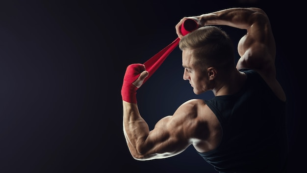 Strong caucasian man wrap hands on black background man is wrapping hands with red boxing wraps isolated on black background strong hands and fist, ready for training and active exercise