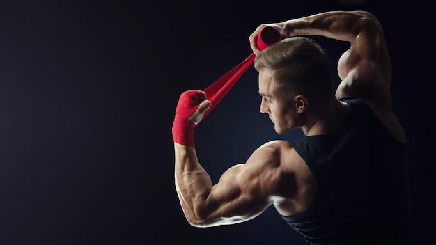 강한 백인 남자가 검은 배경에 손을 감싼 남자는 검은 배경에 격리된 빨간색 권투 랩으로 손을 감싸고 있습니다. 강한 손과 주먹, 훈련 및 활동적인 운동을 위한 준비