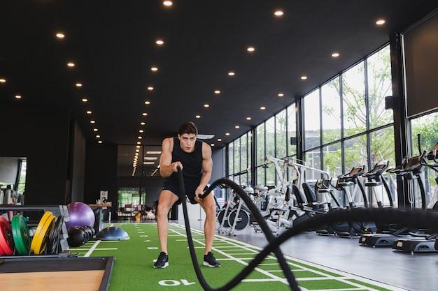 バトルロープを持つ強い白人男性バトルロープは機能的なフィットネスジムで運動します。