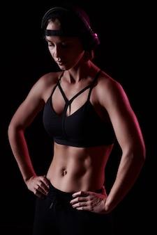 筋肉質の腹部を持つスポーツブラを身に着けている強い白人女性は、黒い背景の上にヘッドフォンで音楽を聴きます。完璧な体型