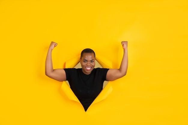 강한. 쾌활 한 아프리카 계 미국인 젊은 여성이 찢어진 된 노란색 종이, 감정 및 표현 포즈.