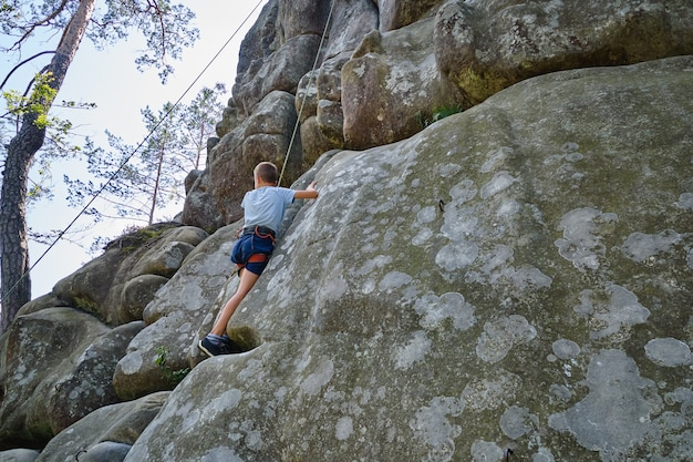 Strong child climber climbing steep wall of rocky mountain. young boy overcoming difficult route. engaging in extreme sports hobby concept.