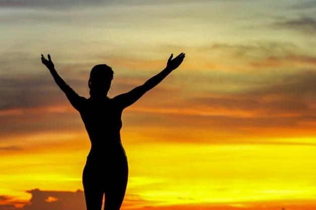 海辺で日の出の強い自信の女性両手を広げて