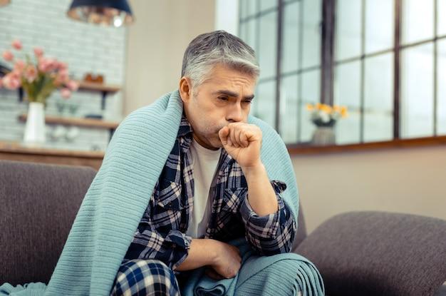 強い咳。風邪の症状がありながら咳をする落ち込んでいる元気のない男
