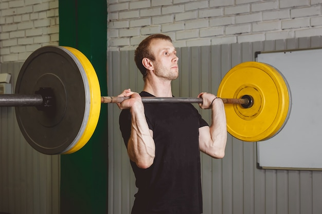 Strong crossfit athlete in a heavy overhead squat lift in a cross-fit box gym