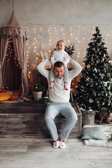 Il forte papà tiene la sua piccola figlia sulle spalle e sorride