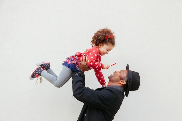 Сильный папа поднимает своего сладкого малыша