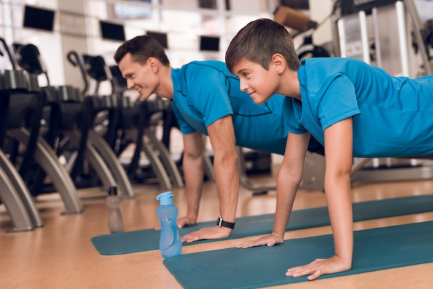 Strong dad and son push-ups in the gym