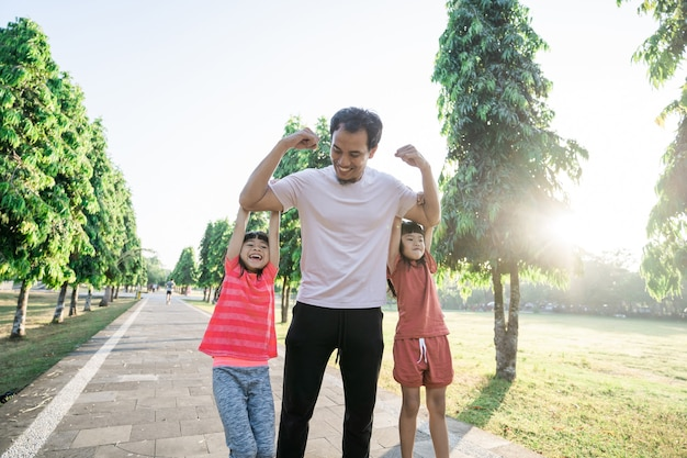 Сильный папа с детьми, висящими на руке во время тренировки